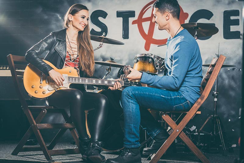 Femme qui joue de la guitare avec son professeur